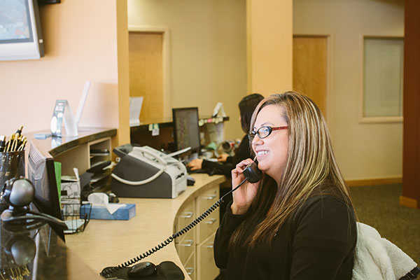 Front desk staff on the phone at dentist office in Pasco, WA